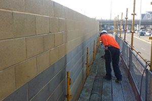 working outside on a wall applying protective coating